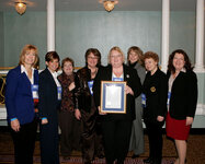Colleen Rocafort (center) receives the 2009 SCC Merit Award from SCC president Linda Rhein (left of Rocafort) and fellow colleagues.