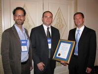 From left: Russel Walters, PhD, Johnson & Johnson and Mike Fevola, PhD, Johnson & Johnson, accept the Best Paper Award from Jesse Kreider of Rhodia.