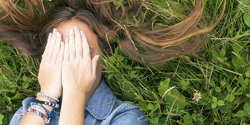 Woman covering face with hands in grass