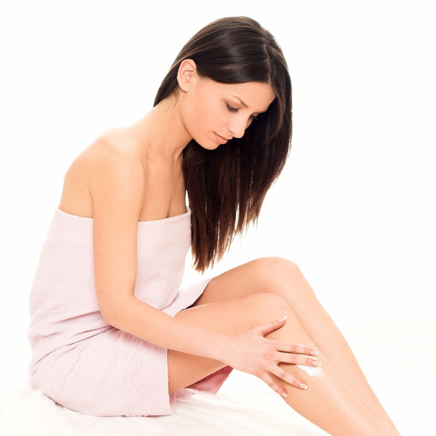 Woman applying lotion to leg 850