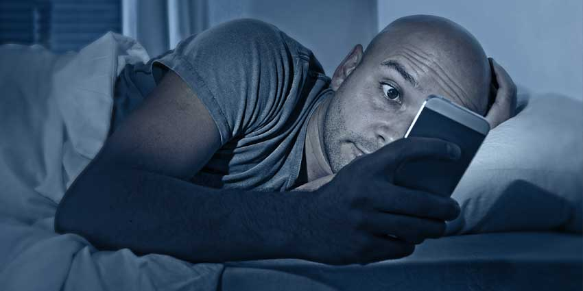 Man on cell phone before bed
