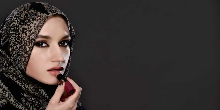 Muslim woman applying lipstick